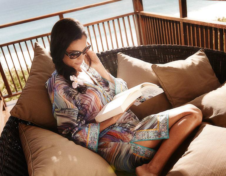 Une jeune femme sur la terrasse du lodge lit un livre avec une vue magnifique sur l'océan en arrière-plan