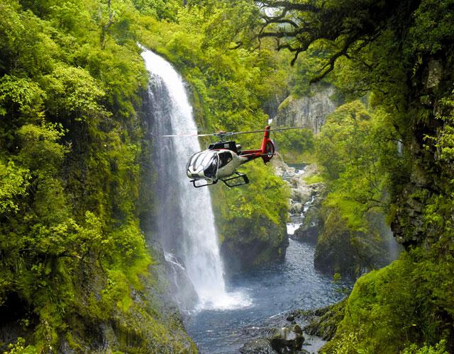 Vue grandiose d'un hélicoptère face à une cascade